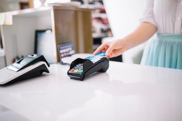 Mujer usando terminal de pago en el mostrador de cajero