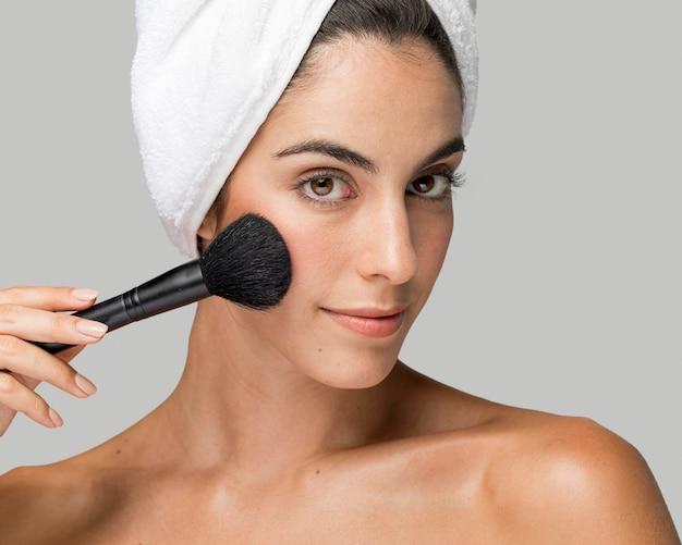 Mujer usando una vista frontal del cepillo de maquillaje