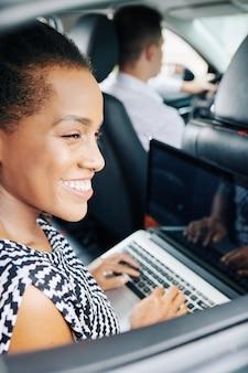 Mujer, usar la computadora portátil, en coche