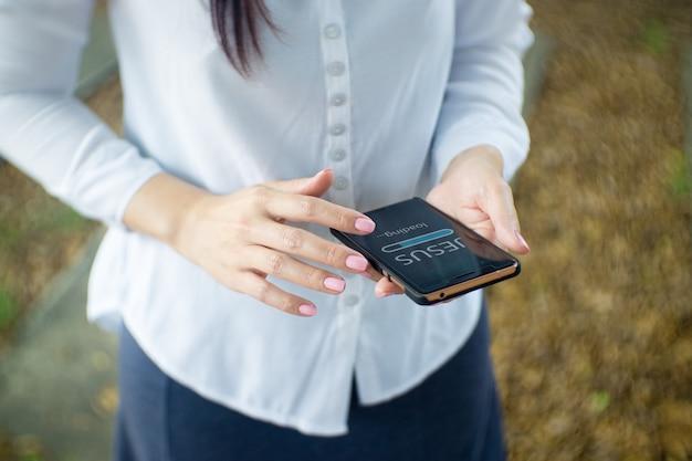 Mujer usar teléfono inteligente en casa. barra de progreso cargando con el texto: jesús en la pantalla del teléfono inteligente. concepto en línea de la iglesia.