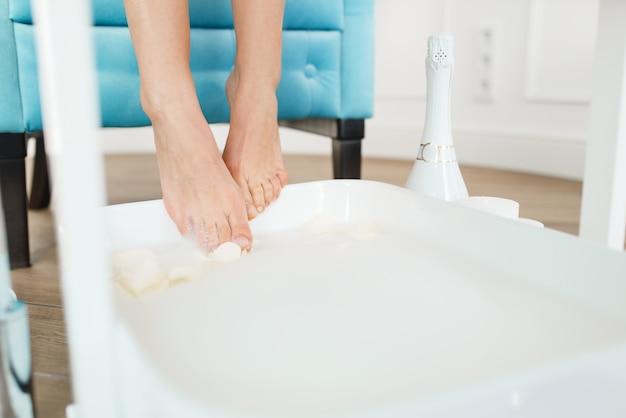 La mujer utiliza un baño de pies con pétalos de rosa blanca, salón de belleza