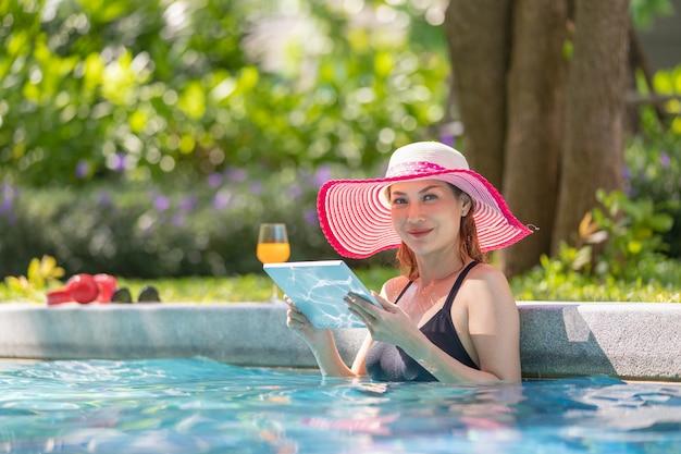 Mujer, utilizar, tableta, computadora, en, piscina
