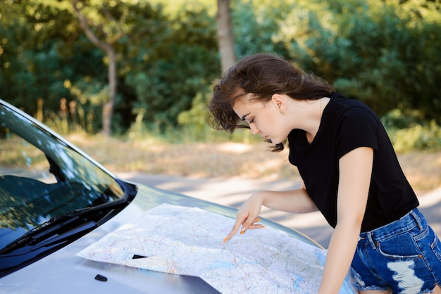 Mujer de vacaciones mirando el mapa para obtener direcciones en el capó de su coche