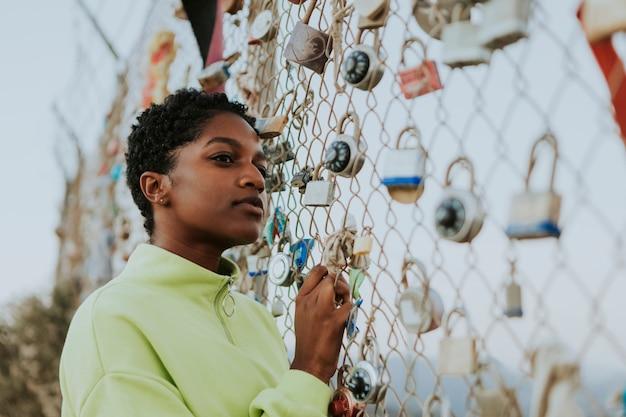 Mujer por una valla con candados en la
