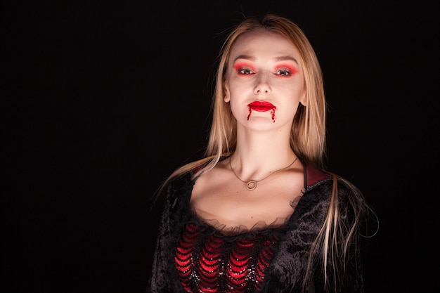 Mujer vampiro malvada con cabello rubio sobre fondo negro. traje de halloween.