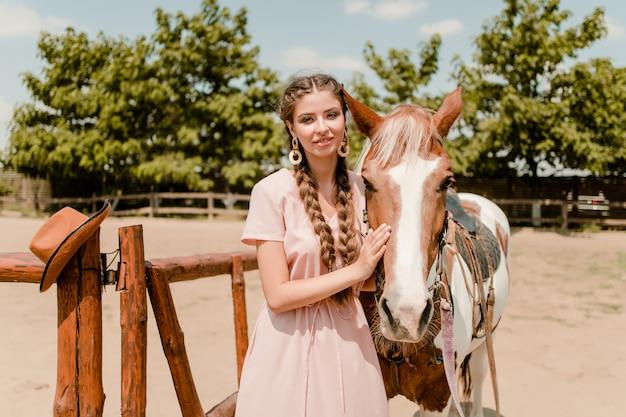Mujer vaquera con un caballo en un rancho