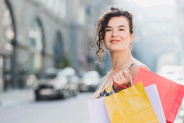 Mujer con varias bolsas de papel de compras felizmente