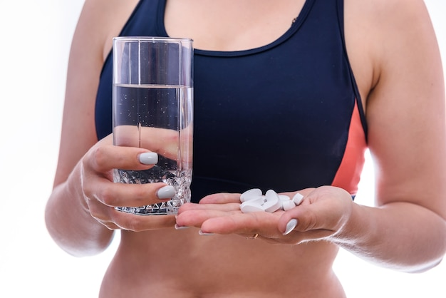 Mujer con vaso de agua y pastillas en botella aislada