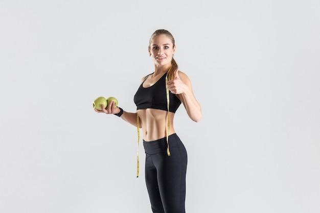 Mujer vegetariana sosteniendo manzana verde y pulgares para arriba. tiro del estudio, fondo gris