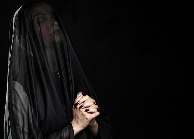Mujer con velo negro y copia espacio