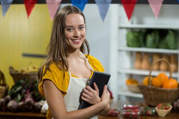 Mujer vendedora con tableta digital en el mostrador de la tienda de comestibles