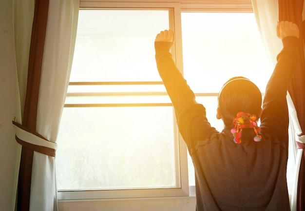 Mujer en la ventana levantando las manos frente a la salida del sol en la mañana, se despierta en la mañana con sunrise.dream suave style.feeling fresco, feliz y disfrutar