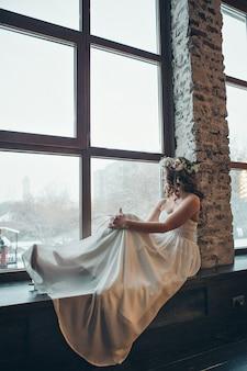 Mujer por la ventana. novia mirando por la ventana, espera al novio. hermosa novia en vestido de novia blanco