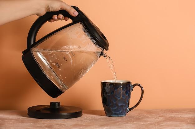 Mujer vertiendo agua hervida caliente de hervidor eléctrico en taza en la mesa