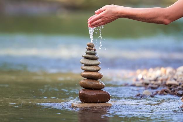 Mujer vertiendo agua sobre piedras rugosas equilibradas como pirámide