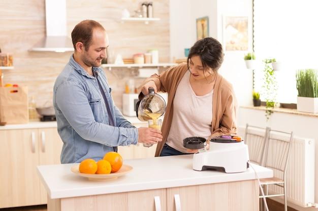 Mujer vertiendo batido nutritivo en vasos para ella y su marido. estilo de vida saludable, despreocupado y alegre, comiendo dieta y preparando el desayuno en una acogedora mañana soleada