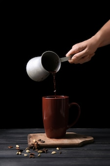 Mujer vertiendo chocolate caliente de cezve en taza sobre mesa de madera