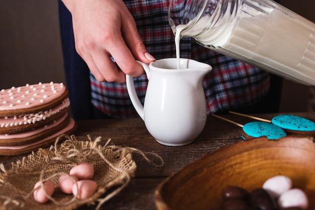 Mujer vertiendo leche en tarro pequeño