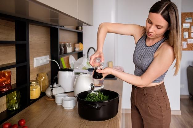 Mujer vertiendo sal en un recipiente con hierbas