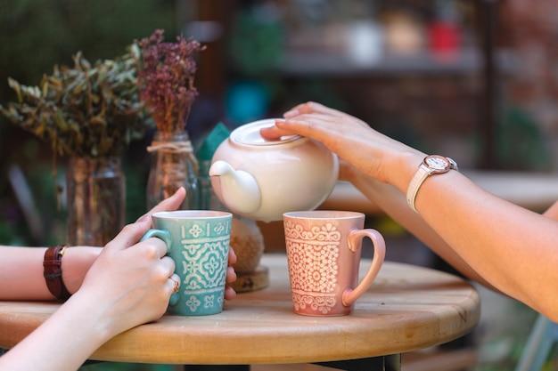 Mujer vertiendo té en el café de la mañana