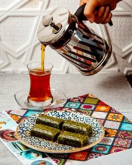 Mujer vertiendo té negro de prensa francesa servido con postre turco