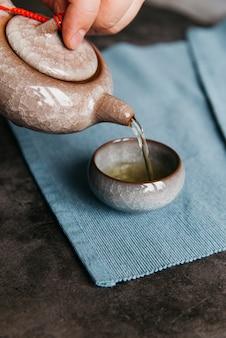 Una mujer vertiendo té de una tetera de cerámica en la taza de té