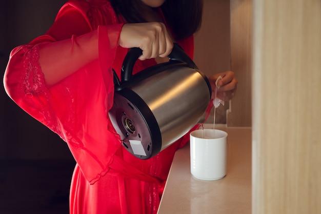 La mujer vestía una larga túnica de satén rojo haciendo té en la cocina por la noche. chica asiática vierte agua caliente en una taza blanca