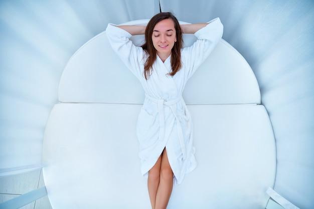 Mujer vestida con albornoz blanco con los ojos cerrados y las manos detrás de la cabeza acostado en una tumbona y disfrutando de un momento de relax y sentirse bien en un balneario de bienestar estilo de vida fácil y satisfacción