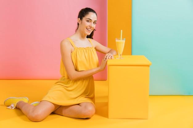Mujer vestida de amarillo con un vaso de jugo