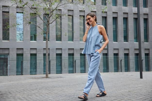 Mujer vestida de azul disfruta de una conversación por teléfono móvil en itinerancia mientras viaja al extranjero hace llamadas con teléfonos inteligentes a través de la aplicación paseos al aire libre cerca de un establecimiento moderno