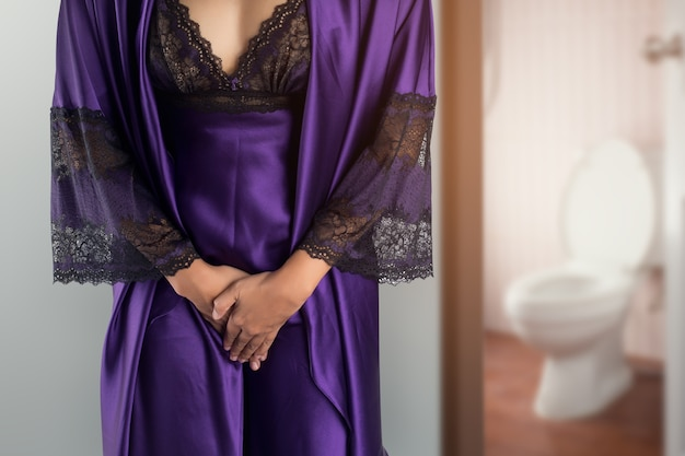 La mujer vestida con una bata de satén púrpura y una bata se despierta para ir al baño