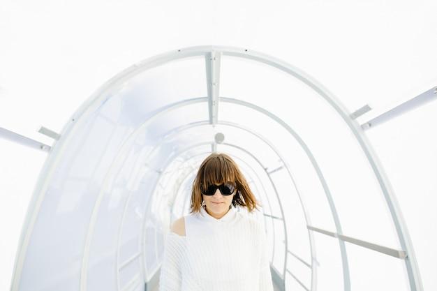 Mujer vestida de blanco atravesando el corredor