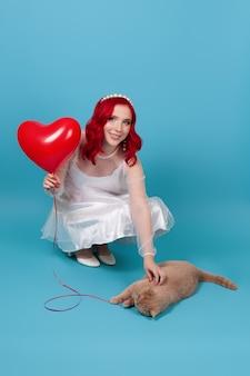 Mujer vestida de blanco sosteniendo un globo volador en forma de corazón, jugando con un gato rojo