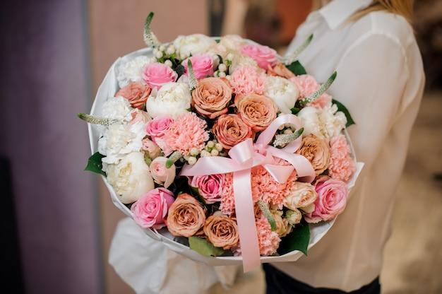 Mujer vestida con una blusa blanca con un ramo de flores