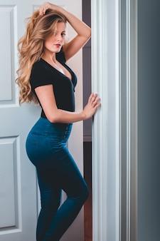 Mujer vestida con blusa negra de pie cerca de la puerta