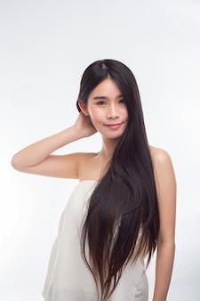 La mujer, vestida con blusas blancas sin tirantes y manos, toca su cabello.
