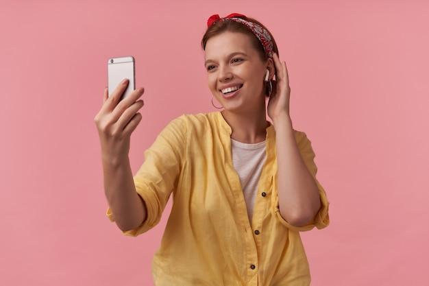 Mujer vestida con camisa amarilla y pañuelo rojo con los brazos gesticula en el teléfono sonriendo a un lado emoción coqueteo sonrisa feliz contento aislado posando en rosa