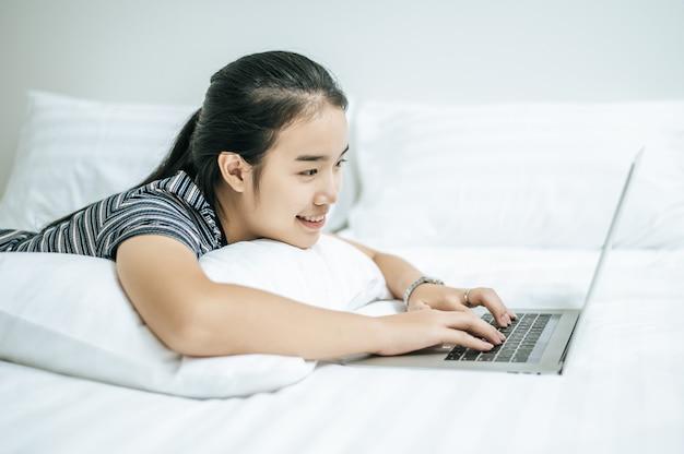 Una mujer vestida con una camisa a rayas en la cama y jugando un portátil.