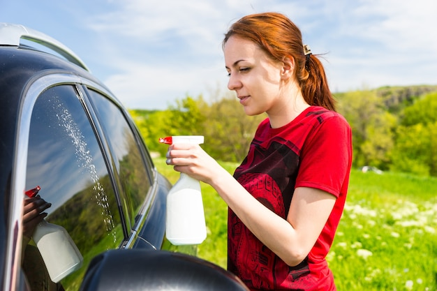Mujer vestida con camisa roja limpieza de ventanas de coche con limpiador de botella de spray en campo verde en día soleado