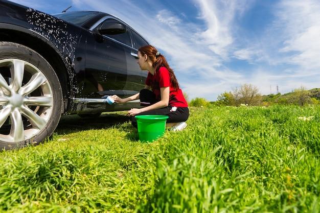 Mujer vestida con camiseta roja lavando vehículo negro en el campo, agachado junto al cubo verde escurriendo una esponja jabonosa en un día soleado