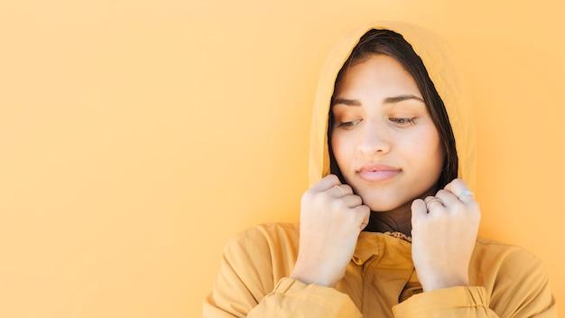 Mujer vestida con chaqueta con capucha de pie contra la superficie amarilla