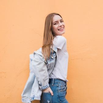 Mujer vestida con chaqueta vaquera y posando junto a la pared beige.