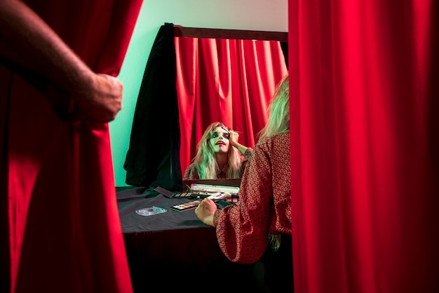 Mujer vestida como un payaso de halloween mirando en el espejo
