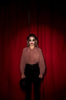 Mujer vestida como un payaso de pie delante de una cortina