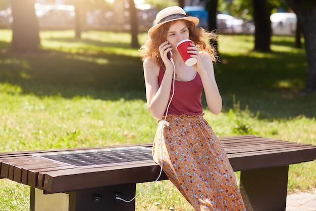 Mujer vestida con falda, camiseta y sombrero, cargando el teléfono inteligente a través de usb al aire libre. carga pública en banco con panel solar en la calle. fuente de electricidad alternativa y concepto de tecnología moderna.