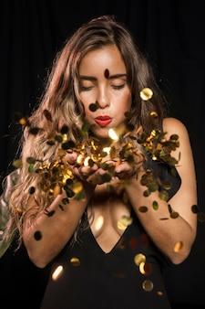 Mujer vestida para fiesta soplando en confeti dorado