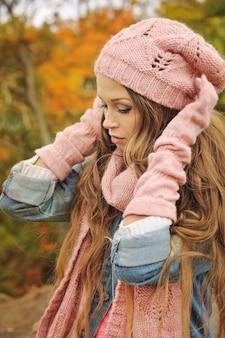 Mujer vestida con gorro de punto rosa, bufanda y guantes en el parque de otoño.