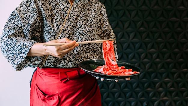 Mujer vestida con un kimono con una rebanada rara de carne wagyu en palillos