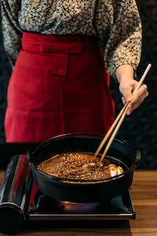 Una mujer vestida con kimono salteado al horno rebanada rara wagyu a5 carne en sopa sukiyaki shoyu por palillos.