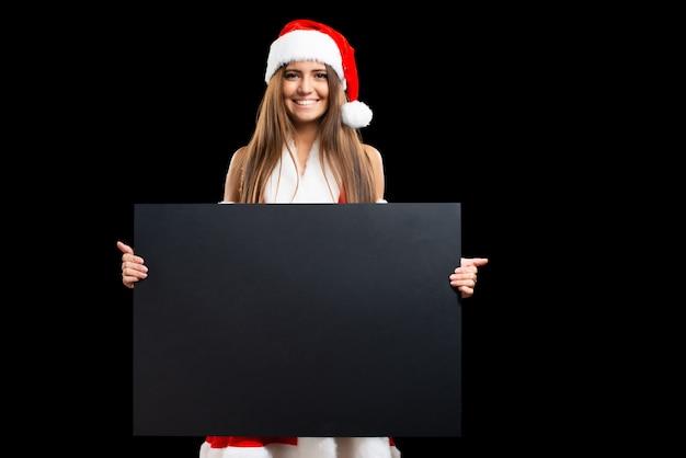 Mujer vestida de navidad sosteniendo un panel blanco